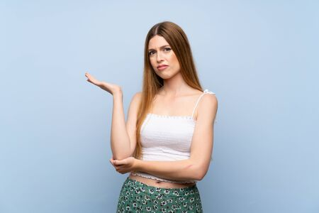 Young woman over isolated blue background unhappy for not understand something 版權商用圖片
