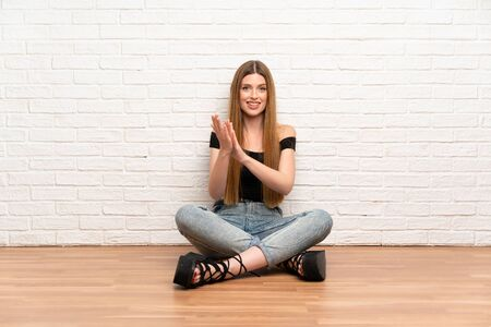 Young woman sitting on the floor applauding Stockfoto - 130559582
