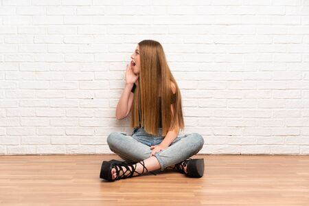 Young woman sitting on the floor shouting with mouth wide open