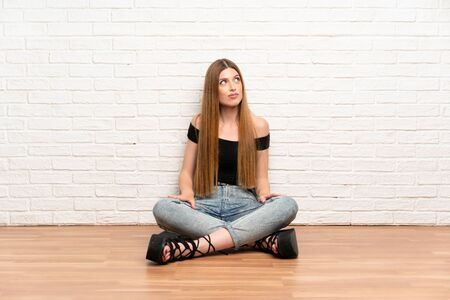 Young woman sitting on the floor standing and looking to the side Stockfoto - 130559668