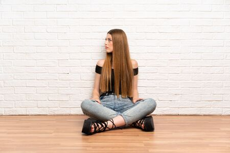 Young woman sitting on the floor looking side