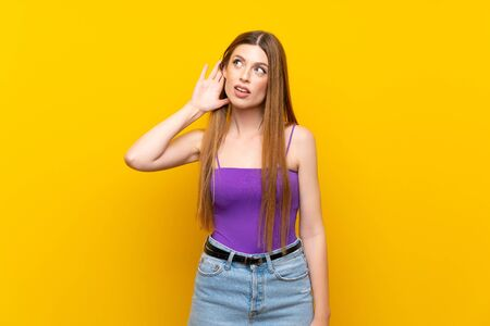 Young woman over isolated yellow background listening to something by putting hand on the ear