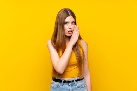 Young woman over isolated yellow background whispering something