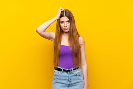 Young woman over isolated yellow background with an expression of frustration and not understanding