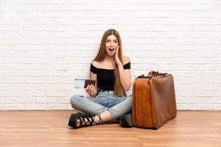 Traveler woman with suitcase and boarding pass with surprise and shocked facial expression 版權商用圖片