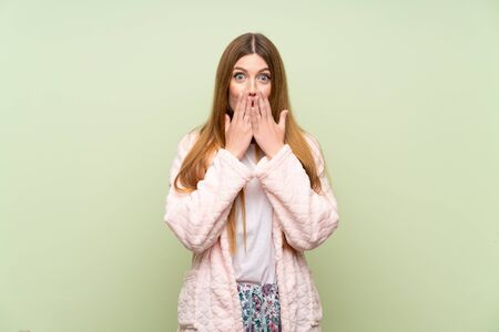Young woman in dressing gown over green wall with surprise facial expression