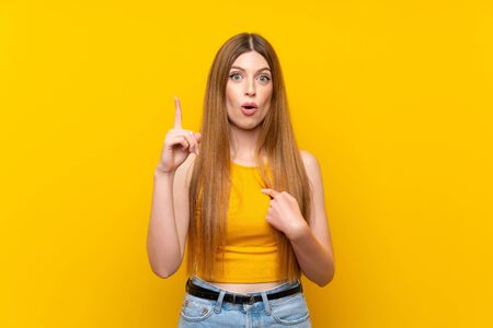 Young woman over isolated yellow background with surprise facial expression