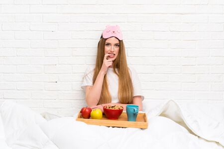 Young woman in dressing gown with breakfast nervous and scared