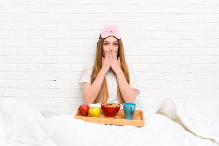 Young woman in dressing gown with breakfast with surprise facial expression
