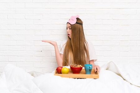 Young woman in dressing gown with breakfast holding copyspace imaginary on the palm Stok Fotoğraf