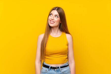 Young woman over isolated yellow background laughing and looking up