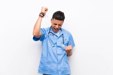 Young surgeon doctor man over isolated white wall celebrating a victory