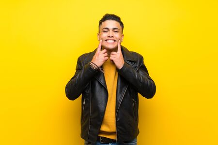 Young man over isolated yellow background smiling with a happy and pleasant expression