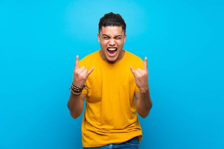 Young man with yellow shirt over isolated blue background making rock gesture