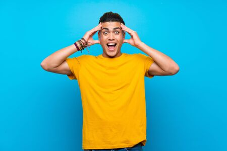 Young man with yellow shirt over isolated blue background with surprise expression