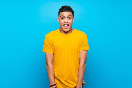 Young man with yellow shirt over isolated blue background with surprise facial expression