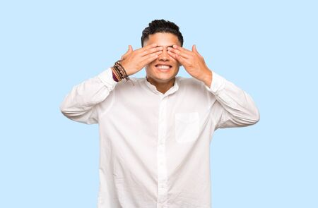 Young man covering eyes by hands on colorful background