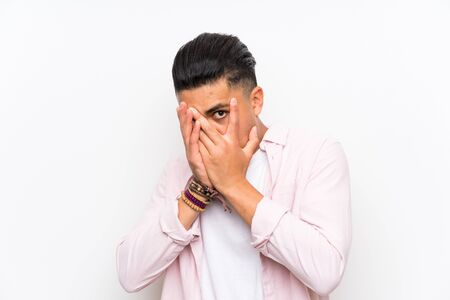 Young man over isolated white wall covering eyes and looking through fingers