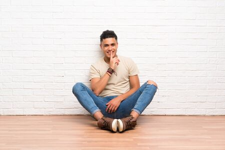 Young man sitting on the floor doing silence gesture