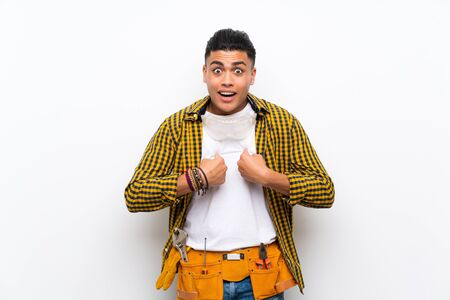 Young electrician man over isolated white wall with surprise facial expression