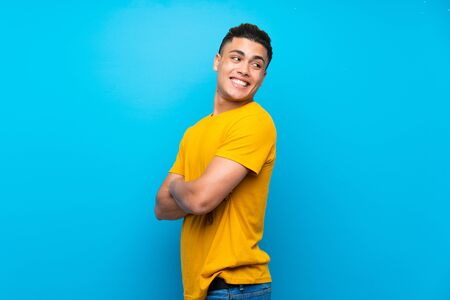 Young man with yellow shirt over isolated blue background with arms crossed and happy