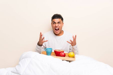 Young man having breakfast in bed unhappy and frustrated with something Stock Photo