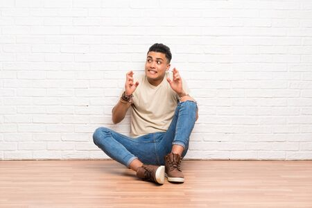 Young man sitting on the floor with fingers crossing