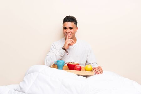 Young man having breakfast in bed doing silence gesture