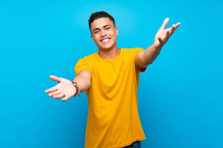 Young man with yellow shirt over isolated blue background presenting and inviting to come with hand