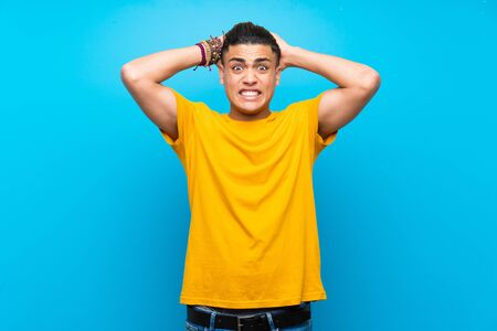Young man with yellow shirt over isolated blue background frustrated and takes hands on head