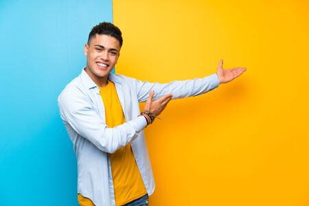 Young man over isolated colorful background extending hands to the side for inviting to come