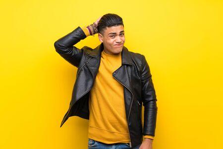 Junger Mann über isoliertem gelbem Hintergrund, der beim Kopfkratzen Zweifel hat Standard-Bild