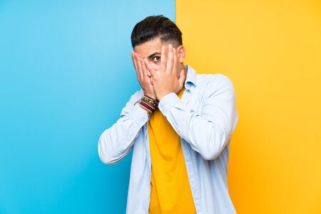 Young man over isolated colorful background covering eyes and looking through fingers