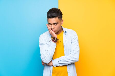 Young man over isolated colorful background unhappy and frustrated