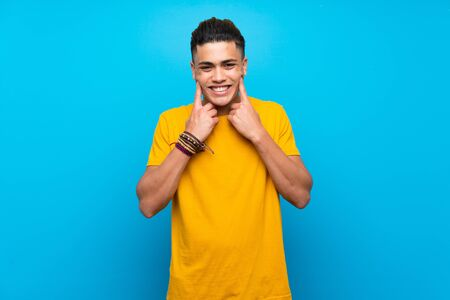 Young man with yellow shirt over isolated blue background smiling with a happy and pleasant expression Stok Fotoğraf