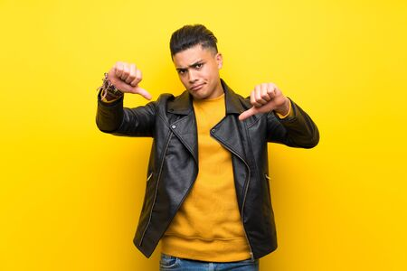 Young man over isolated yellow background showing thumb down