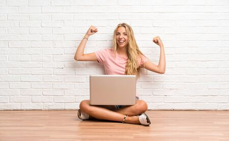 Young blonde student girl with a laptop on the floor celebrating a victory