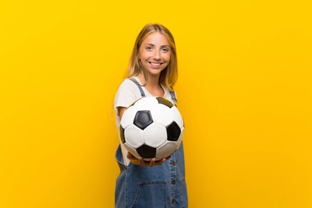 Blonde young woman over isolated yellow background holding a soccer ball