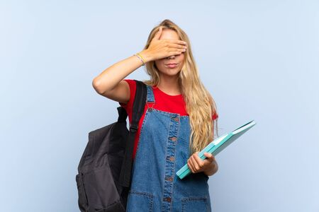Young blonde student woman over isolated blue wall covering eyes by hands
