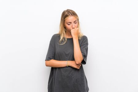 Blonde young woman over isolated white background having doubts