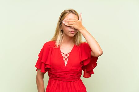 Blonde young woman over isolated green background covering eyes by hands