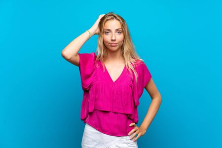 Blonde young woman over isolated blue background with an expression of frustration and not understanding