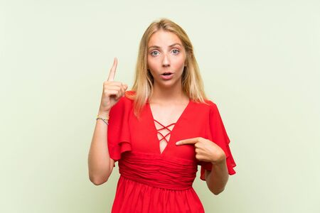Blonde young woman over isolated green background with surprise facial expression