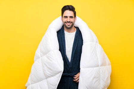 Handsome man in pajamas over isolated yellow wall Stock fotó