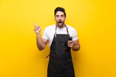 Young hairdresser man over isolated yellow background surprised and pointing finger to the side