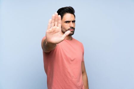 Handsome young man in pink shirt over isolated blue background making stop gesture