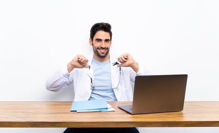 Young doctor man with his laptop over isolated wall proud and self-satisfied