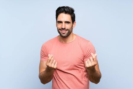 Handsome young man in pink shirt over isolated blue background making money gesture