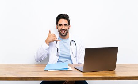 Young doctor man with his laptop over isolated wall making phone gesture