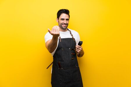 Young hairdresser man over isolated yellow background inviting to come with hand. Happy that you came Фото со стока